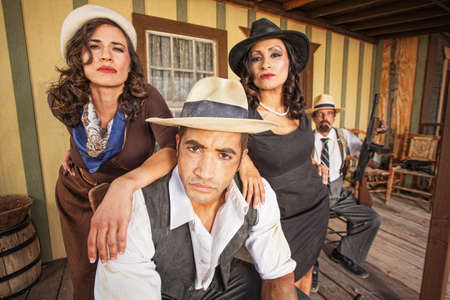 tommy: Tough 1920s gangster surrounded by pretty women outside Stock Photo