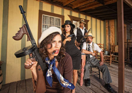 man holding gun: Tough gangster woman with cigar and submachine gun Stock Photo