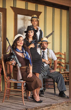 tough woman: Four tough male and female gangsters sitting with weapons Stock Photo
