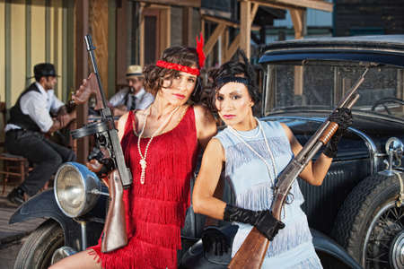 antique rifle: 1920s attractive female gangsters with rifle and submachine gun Stock Photo