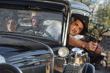 gangster with gun: 1920s vintage gangsters drive by shooting