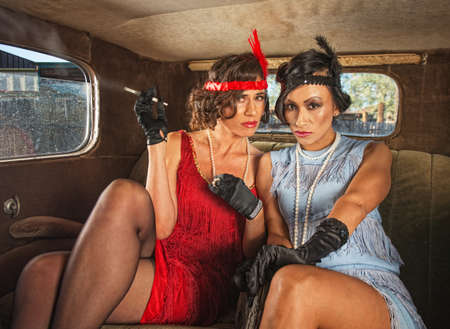 Two serious retro flapper women smoking in antique car photo