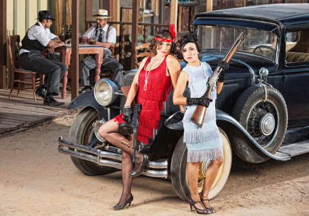 antique car: 1920s vintage gangster women holding weapons near car Stock Photo