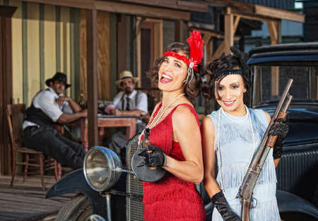 women with guns: Pair of laughing 1920s gangster women with guns Stock Photo