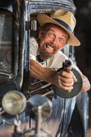 antique car: Bearded man firing submachine gun from vintage 1920s car