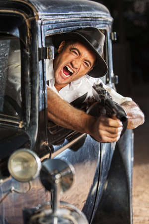 gangster with gun: Yelling man firing submachine gun from vintage 1920s car Stock Photo