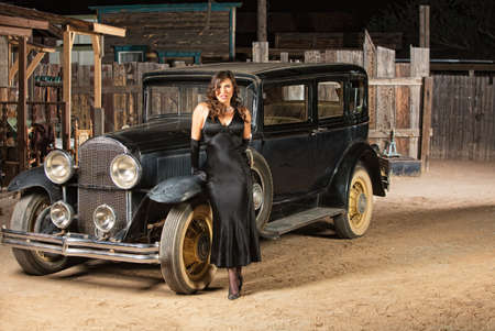 sultry: Sultry woman in black next to vintage automobile