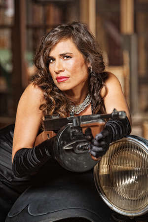 smirking: Smirking woman in black dress holding submachine gun Stock Photo
