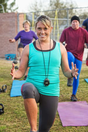 Exercise instructor leading adults in fitness outdoors photo