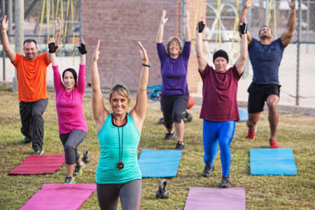 Group of active adults stretching outdoors with mats photo