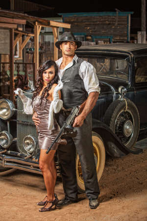Handsome muscular 1920s gangster with lady in mini skirt photo
