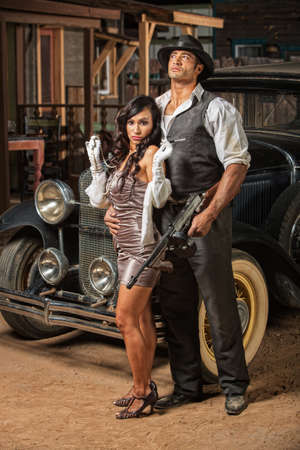 tough: Beautiful woman in mini skirt with tough armed gangster