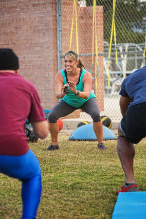 boot camp: Cheerful boot camp fitness instructor squatting