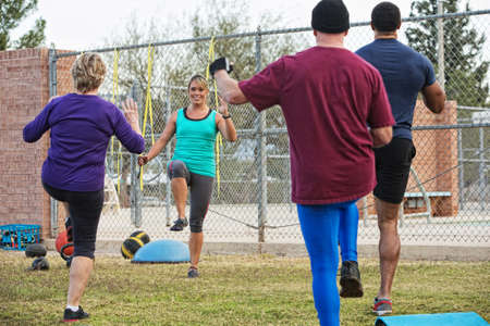 Active adults with instructor performing boot camp exercises photo