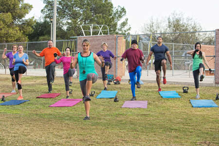 Mixed group of mature adults in boot camp exercise