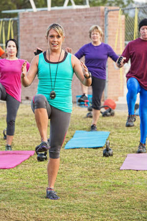 Smiling workout instructor with diverse group outdoors photo