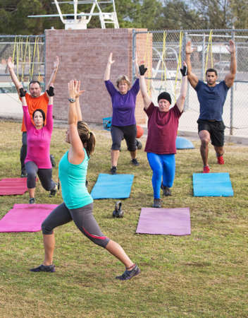 Mature adult boot camp exercise group stretching outdoors photo