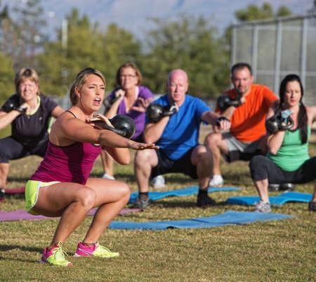 Boot camp fitness trainer schreeuwen tijdens squat oefeningen