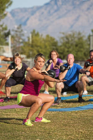 boot camp: Cheerful fitness instructor leading group of adults