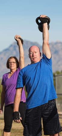 Fit pair of middle aged people exercising with weights photo