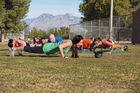 Young woman leading group in push up exercises outdoors photo