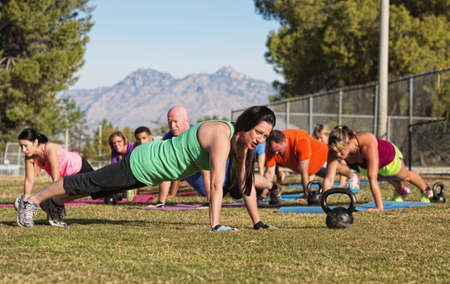 Group of adults doing push up exercises outdoors photo
