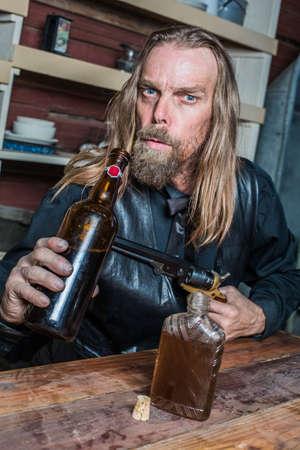 deadpan: Drunk Western Man Aims Gun Towards Bottle as he Sits at Table