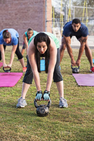 boot camp: Beautiful woman leading group with kettle bell weights Stock Photo