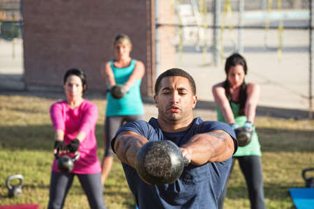 Four people exercising in outdoor boot camp with kettle bells photo