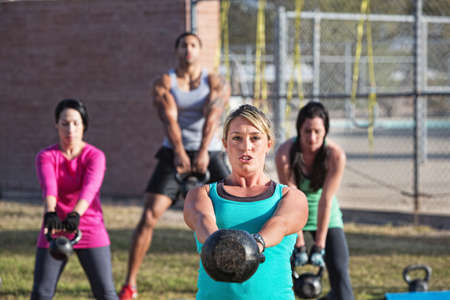 Fit woman leading group of adults with weights photo