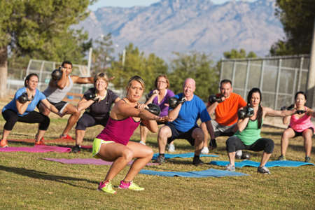boot camp: Serious boot camp exercise class squatting with weights