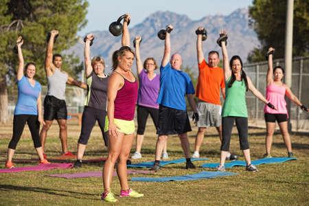 Gemengde groep van mannen en vrouwen het heffen van gewichten, buitenshuis