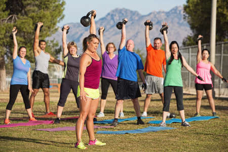 Mixed group of men and women lifting weights outdoors photo
