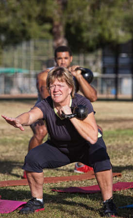 boot camp: Strong middle aged woman squatting with kettle bell weights