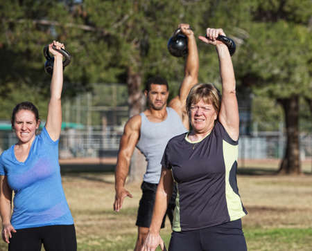 Mature white female exercising with kettle bell weights photo