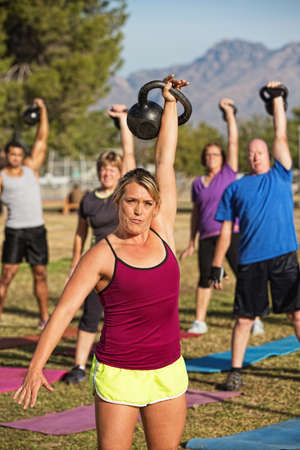 Athletic woman teaching boot camp fitness class outdoors photo