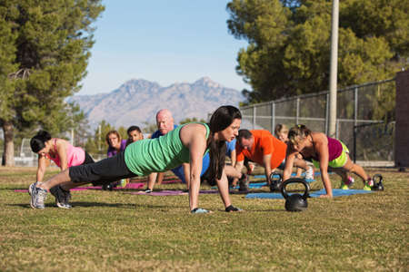 Fitness instructor leading group in push up exercises outdoors photo