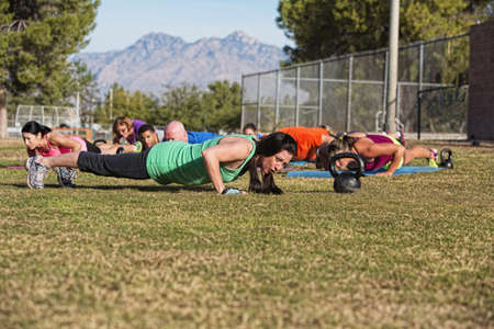 Boot camp fitness group doing push up exercises outdoors photo