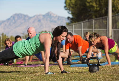 training group: Young woman leading group in push up exercises near mountains