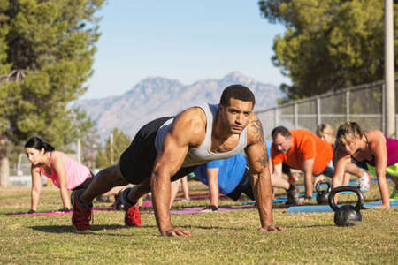 boot camp: Muscular instructor and group exercising near mountains