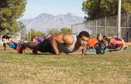 Outdoor exercise boot camp fitness group near mountain photo