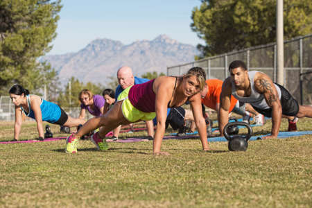 Blond fitness instructor leading push-ups near mountain photo