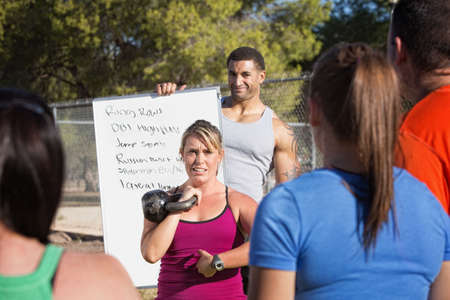Boot camp fitness instructors explaining exercises to a class photo