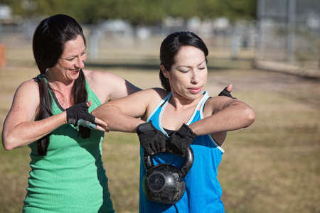Two women working out with kettle bell weights photo