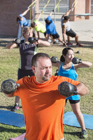 boot camp: Fit mature adults exercising with weights in boot camp fitness class