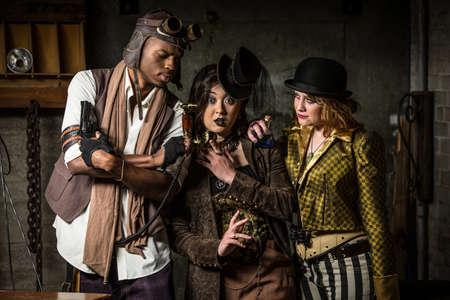 anachronistic: Three Steampunks with Underground Lair with Retro Phone Stock Photo