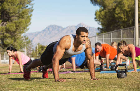 Strong man leading push-ups with exercise group photo
