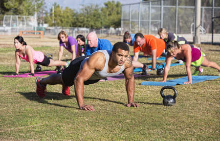 Group of adults exercising in outdoor boot camp photo