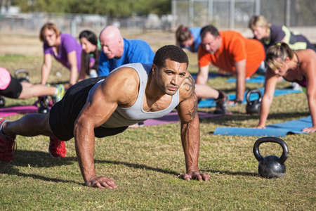 Group of serious adults doing push-ups outdoors