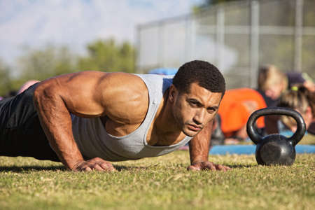 Handsome Black man with large biceps doing push-ups outdoors photo